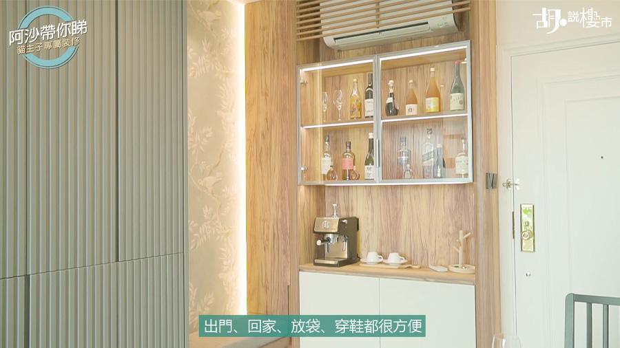 設計師將大門右邊的到頂櫃拆除,重造一個木色的到頂儲物櫃及鞋櫃,並在旁邊放置小凳子